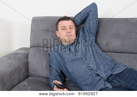 Man Thinking On The Sofa Alone At Home