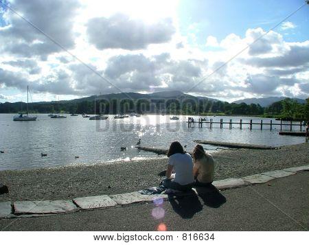 Teo 女孩坐在湖边。