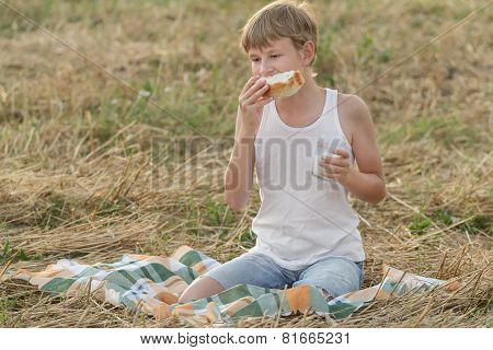 Teenage Farmer Boy Eating Fresh White Bread