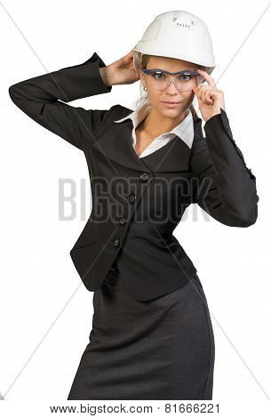 Businesswoman posing in hard hat and protective glasses