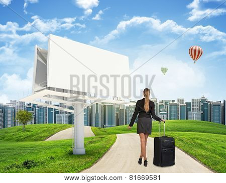 Businesswoman with suitcase on the road
