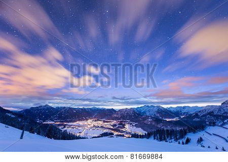 mountain view over illuminated valley in winter at night