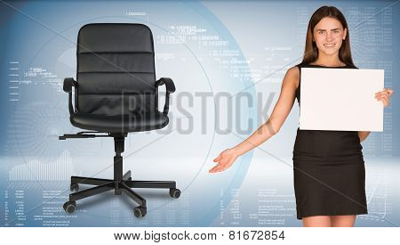 Businesswoman holding blank paper sheet, showing empty office chair beside. Hi-tech graphs as backdr