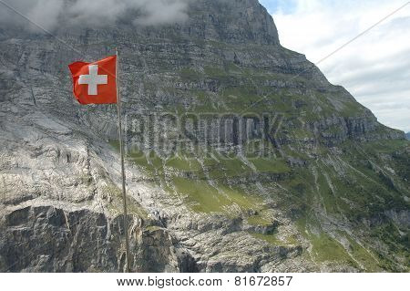 Swiss Flag High In Mountains Nearby Grindelwald In Switzerland.