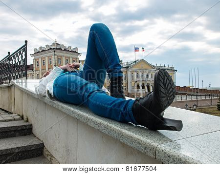 Photo of young woman lying on the railing
