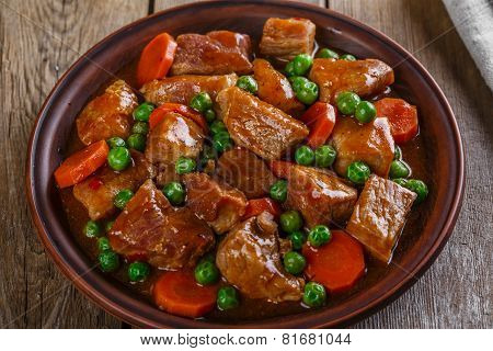 beef stew with peas and carrots on a plate