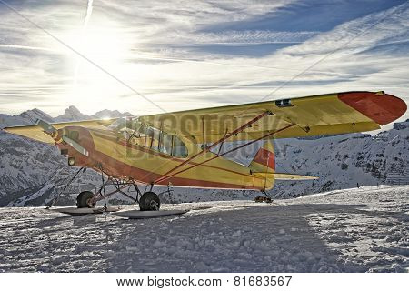 Yellow Airplane At The Mountain Airfield In Swiss Alps