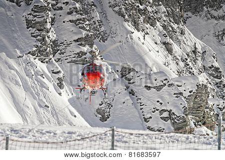 Red Helicopter Landing At Swiss Ski Resort Near Jungfrau Mountain