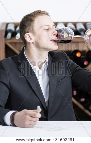 Male Winemaker Tasting A Red Wineglass.