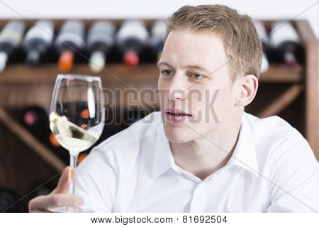 Man Shaking A White Wineglass.