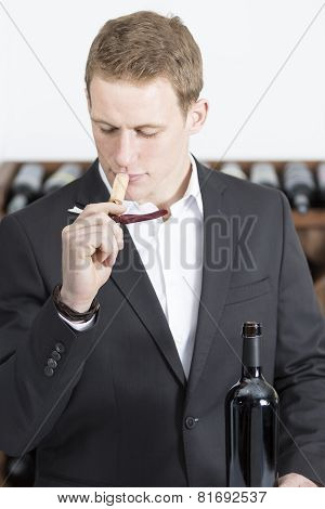 Man Smelling A Cork.