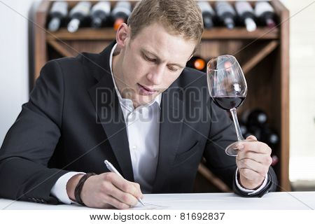 Man Writing On A Wine Tasting Sheet.