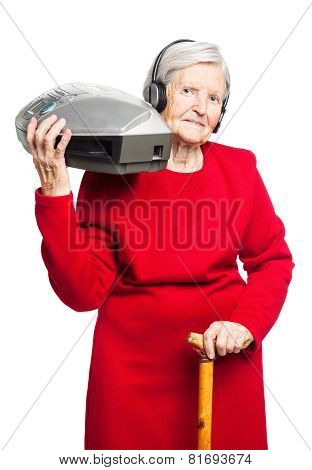 Senior woman listening to music on stereo recorder