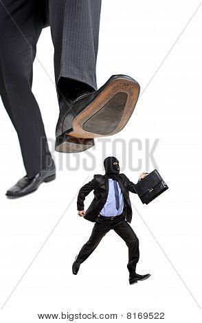 An afraid burglar running away from a big foot