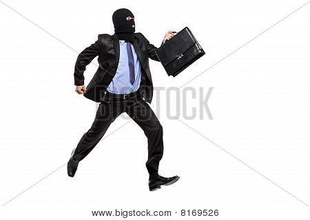 A burglar with robbery mask running away