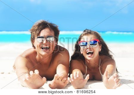 close up of young beautiful couple laughing at beach