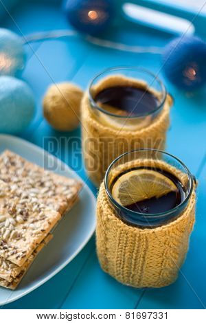 Two Cups Of Delicious Tea In Knitted Sweater Yellow On Blue Background And Cookies