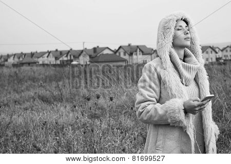 woman listens to music on her smartphone