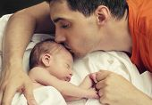 foto of sleeping  - Father kissing his baby boy head while his sleeping and holding hands - JPG