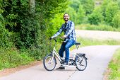 picture of tandem bicycle  - Man riding tandem bike on country lane - JPG