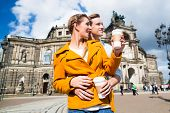 image of takeaway  - Tourist couple at Semperoper in Dresden having walk with coffee to takeaway - JPG