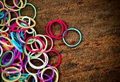 picture of loom  - colorful Rainbow loom bracelet rubber bands fashion on old wood background with space on the left - JPG