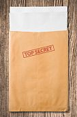 stock photo of top-secret  - Open yellow envelope with top secret stamp and blank papers on wooden table clipping path - JPG