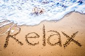 pic of relaxing  - The word RELAX written into the sand on a tropical sandy beach in paradise - JPG