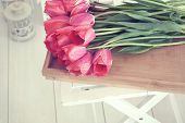 stock photo of trays  - Vintage shabby chic photo of bouquet of spring tulips on a wooden tray on white wooden floor - JPG