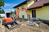 picture of crusher  - A house is being forclosed and demolished with a crusher - JPG