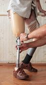 image of prosthetics  - Hands machinery governing prosthetic leg on man - JPG
