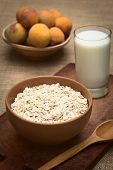 stock photo of oats  - Bowl full of rolled oats with a glass of milk and peaches in the back photographed with natural light  - JPG