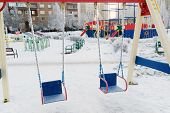 image of snow-slide  - snow covered swing and slide at a playground in winter - JPG
