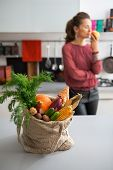 picture of local shop  - Closeup on shopping bag with fresh vegetables from local market and young housewife in background - JPG