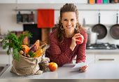 picture of check  - Portrait of happy young housewife holding grocery shopping checks in kitchen - JPG