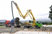 foto of concrete pouring  - Builder uses a concrete pump to direct wet concrete into the foundations of a large building - JPG