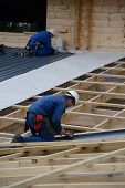 picture of purlin  - Builders complete the roofing iron on a major construction job - JPG