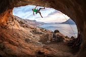foto of cave  - Male rock climber climbing along a roof in a cave at sunset - JPG