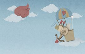 stock photo of cupid  - Cupid shoot bow in hot air balloon on sky made from recycled paper craft - JPG