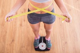 stock photo of measurement  - Top view of pretty slim woman with measure around her body is standing on the scales.