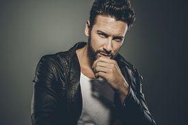 foto of jacket  - Cool seductive man in black leather jacket flirting and looking at camera - JPG
