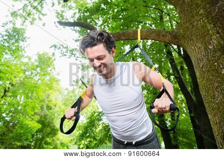 man exercising with suspension trainer sling in City Park under summer trees for sport fitness