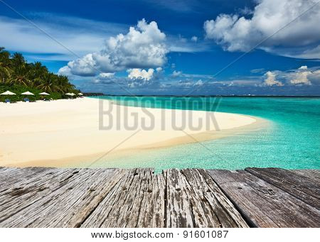Beautiful island beach and old wooden pier at Maldives
