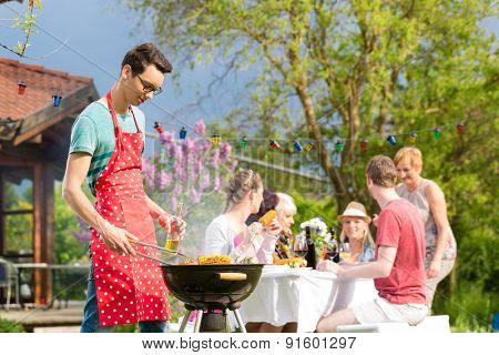 Family and friends having bbq at garden party, man in the foreground on grill, in background people drinking and eating