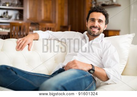 Portrait of a smiling man relaxing on the couch in his home