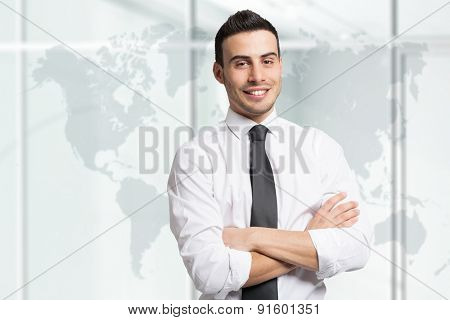 Portrait of a young smiling businessman in front of a world map