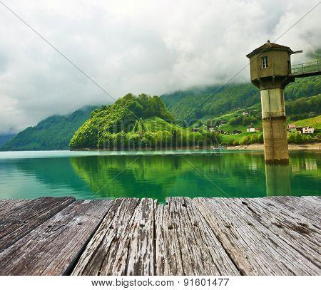Beautiful emerald mountain lake in Switzerland under low clouds
