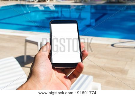 Hand Holding Smart Phone On Poolside