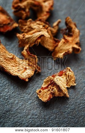 Dried Galangal Root In Close Up On Dark Stone