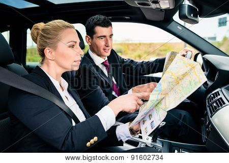 Business couple in car travelling talking to each other